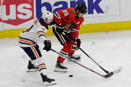 Kris Russell, Patrick Kane. Edmonton Oilers defenseman Kris Russell, left, and Chicago Blackhawks right wing Patrick Kane vie for the puck during the first period of an NHL hockey game in Chicago