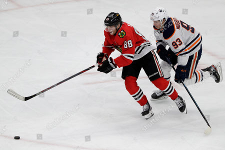 Patrick Kane, Ryan Nugent-Hopkins. Chicago Blackhawks right wing Patrick Kane, left, and Edmonton Oilers center Ryan Nugent-Hopkins chase the puck during the third period of an NHL hockey game in Chicago, . The Blackhawks won 4-3