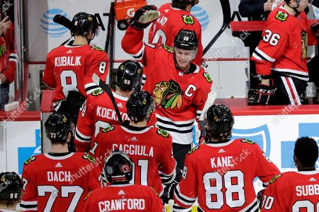 Chicago Blackhawks center Jonathan Toews. facing camera, celebrates with teammates after the Blackhawks defeated the Edmonton Oilers 4-3 in an NHL hockey game in Chicago