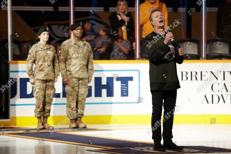 Craig Morgan, right, sings the national anthem before an NHL hockey game between the Predators and the Dallas Stars, in Nashville, Tenn. Morgan, who served in the Army, sang on a Military Appreciation Night