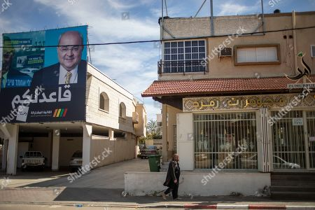 """Israeli Arab woman walks past an election campaign poster showing Israeli Politician Ahmad Tibi of the Joint List in Tira, Israel. A surge in Arab voter turnout was key to depriving Prime Minister Benjamin Netanyahu and his nationalist allies of a parliamentary majority in this week's Israeli election. Undercutting Netanyahu's ambitions was celebrated as sweet payback in the nearly 2 million-strong minority that the hard-line leader had relentlessly tried to tarnish as disloyal to the state. The Arabic reads, """"I sit with you"""