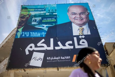 """Israeli Arab Fadila Maha walks past an election campaign poster showing Israeli Politician Ahmad Tibi of the Joint List in Tira, Israel. A surge in Arab voter turnout was key to depriving Prime Minister Benjamin Netanyahu and his nationalist allies of a parliamentary majority in this week's Israeli election. Undercutting Netanyahu's ambitions was celebrated as sweet payback in the nearly 2 million-strong minority that the hard-line leader had relentlessly tried to tarnish as disloyal to the state. The Arabic reads """"I sit with you"""