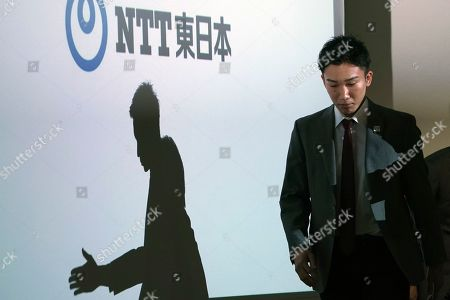 Japanese badminton player Kento Momota walks in the venue of a press conference, in Tokyo. Badminton men's singles world champion and world number one Momota was injured at a traffic accident In January this year in Malaysia