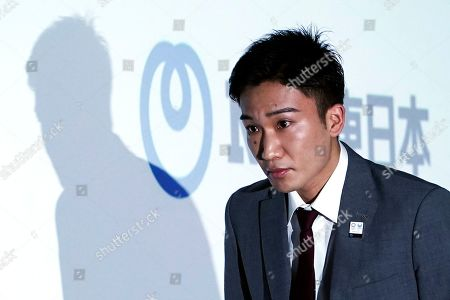 Stock Photo of Japanese badminton player Kento Momota walks in the venue of a press conference, in Tokyo. Badminton men's singles world champion and world number one Momota was injured at a traffic accident In January this year in Malaysia