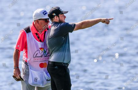 Tyrell Hatton of England (R) and his caddie Mick Donaghy (L) plan Hatton's next shot after he hit onto the water by the third hole during the second round of the Arnold Palmer Invitational golf tournament at Bay Hill Club & Lodge in Orlando, Florida, USA, 06 March 2020.