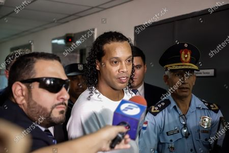 Ronaldo de Assis Moreira, a.k.a. Ronaldinho (C), arrives at the Palace of Justice to appear before Judge Mirko Valinotti, in Asuncion, Paraguay, 06 March 2020. Brazil's former international Ronaldinho and his brother Roberto appeared on 06 March before the judge that will decide if they benefit from a procedural exit that separates them from the open cause after entering Paraguay with false passports. The appeal to this 'abbreviated procedural exit' was granted on 05 March by the Prosecutor's Office to the two brothers and it was because both contributed 'relevant data' to the investigation, as explained by the prosecutor of the case, Federico Delfino.