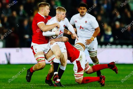 George Barton of England U20 is tackled by Ben Carter of Wales U20