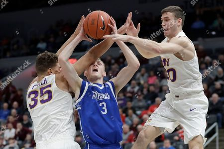 Drake's Garrett Sturtz (3) tries to shoot between Northern Iowa's Noah Carter (35) and Spencer Haldeman during the first half of an NCAA college basketball game in the quarterfinal round of the Missouri Valley Conference men's tournament, in St. Louis