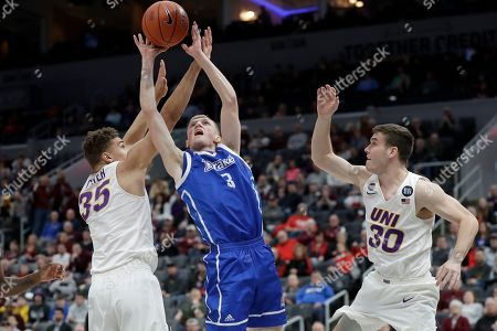 Drake's Garrett Sturtz (3) tries to shoot between Northern Iowa's Noah Carter (35) and Spencer Haldeman (30) during the first half of an NCAA college basketball game in the quarterfinal round of the Missouri Valley Conference men's tournament, in St. Louis