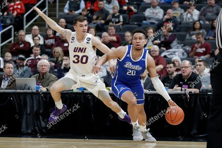Drake's Jonah Jackson (20) dribbles as Northern Iowa's Spencer Haldeman (30) defends during the first half of an NCAA college basketball game in the quarterfinal round of the Missouri Valley Conference men's tournament, in St. Louis
