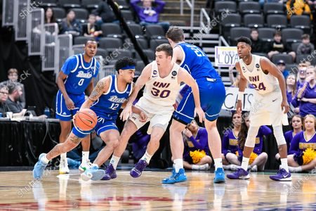 Drake Bulldogs guard Roman Penn (12) uses the screen of Drake Bulldogs forward Liam Robbins (21) to try and get away from the defense of Northern Iowa Panthers guard Spencer Haldeman (30) in the second round of the Missouri Valley Conference Menâ€s Tournament between the University of Northern Iowa and Drake. Held at The Enterprise Center in St. Louis, MO Richard Ulreich/CSM
