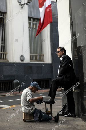 Stock Image of A shoe shiner works on a client's shoes outside the Foreign Ministry where a wake will be held for Javier Perez de Cuellar in Lima, Peru, . Cuellar was a two-term United Nations secretary-general who brokered a historic cease-fire between Iran and Iraq in 1988 and who in later life came out of retirement to help re-establish democracy in his Peruvian homeland