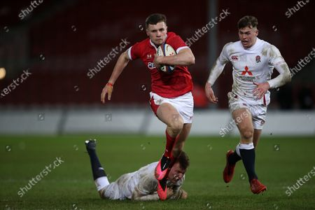 Mason Grady of Wales is tackled by Jack Clement of England.