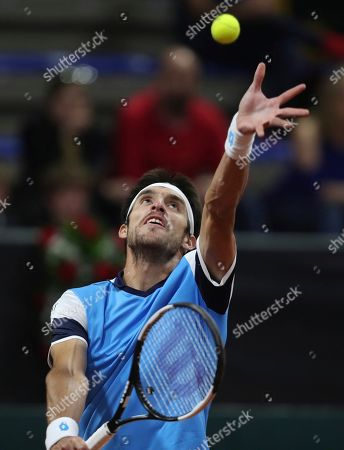 Leonardo Mayer of Argentina serves against Daniel Galan of Colombia during their Davis Cup Rakuten qualifiers tennis match in Bogota, Colombia, Friday, March, 6, 2020