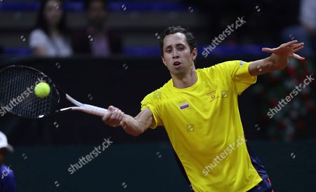 Stock Image of Daniel Galan of Colombia returns a ball to Leonardo Mayer of Argentina during their Davis Cup Rakuten qualifiers tennis match in Bogota, Colombia, Friday, March, 6, 2020