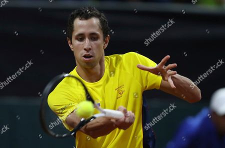 Stock Photo of Daniel Galan of Colombia returns a ball to Leonardo Mayer of Argentina during their Davis Cup Rakuten qualifiers tennis match in Bogota, Colombia, Friday, March, 6, 2020