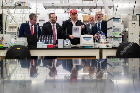 Donald Trump, Robert Refield, Steve Monroe, Alex Azar. President Donald Trump holds a picture as he speaks during a meeting with Gov. Brian Kemp, R-Ga., left, Health and Human Services Secretary Alex Azar, Centers for Disease Control and Prevention Director Dr. Robert Redfield, Associate Director for Laboratory Science and Safety Steve Monroe, about the coronavirus at the Centers for Disease Control and Prevention Director, in Atlanta