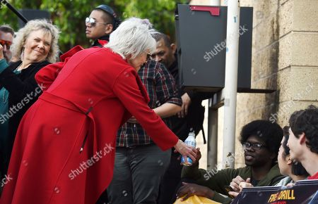 Jane Fonda, left, hands a bottle of water to a Fire Drill Fridays participant protesting neighborhood oil drilling by blocking the entrance to an oil field in the Wilmington neighborhood of Los Angeles