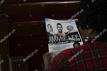 A spectator reads the program during Jimmie Lee Jackson day at Marion Baptist in Marion, Ala