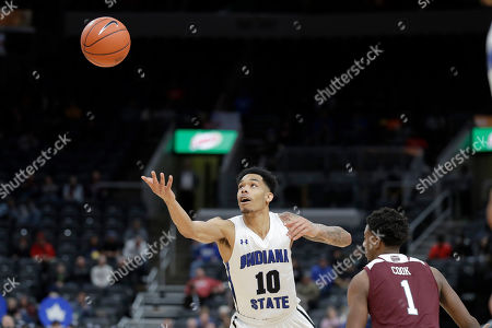 Indiana State's Christian Williams (10) reaches for the ball as Missouri State's Keandre Cook (1) defends during the first half of an NCAA college basketball game in the quarterfinal round of the Missouri Valley Conference men's tournament, in St. Louis