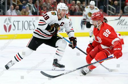 Chicago Blackhawks center Jonathan Toews (19) takes the puck around Detroit Red Wings center Sam Gagner (89) during the third period of an NHL hockey game, in Detroit