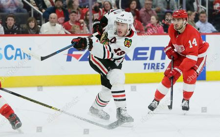Chicago Blackhawks center Jonathan Toews (19) takes a shot on goal as Detroit Red Wings center Robby Fabbri (14) looks on during the third period of an NHL hockey game, in Detroit