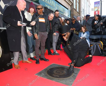 Jazzie B, founder and leading light of the Soul II Soul collective Kneels next to a stone during the Music Walk Of Fame Soul II Soul stone unveiling, the fourth stone to be placed on Camden High Street.