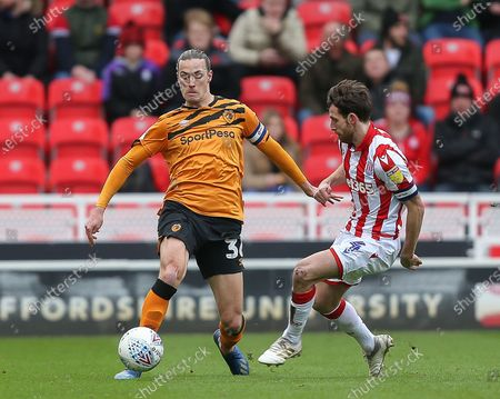 Jackson Irvine of Hull City protects the ball from Joe Allen of Stoke City.