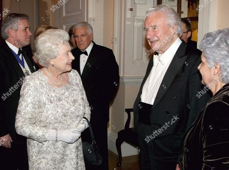 Queen Elizabeth II is greeted by conductor Sir Colin Davis
