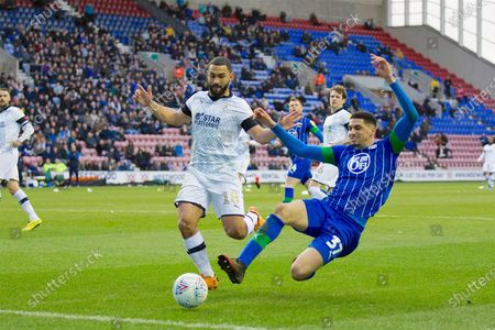 Wigan Athletic defender Leon Balogun challenged by Luton Town defender Cameron Carter-Vickers during the EFL Sky Bet Championship match between Wigan Athletic and Luton Town at the DW Stadium, Wigan