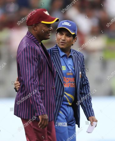 West Indies Legends' Brian Lara and India Legends' Sachin Tendulkar walks during a toss ahead of the start of the Road Safety World Series cricket match in Mumbai, India