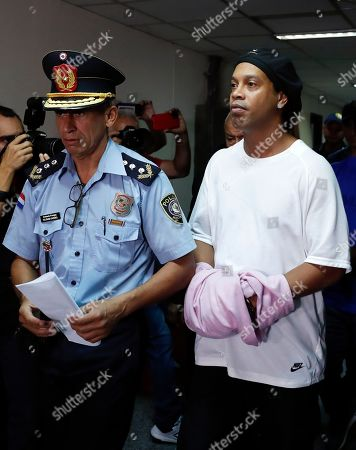 Former soccer star Ronaldinho walks handcuffed and escorted by a police officer to declare to judge Clara Ruiz Diaz at Justice Palace in Asuncion, Paraguay,. Ronaldinho and his brother Roberto were alleged to enter to the country with a false Paraguayan passport