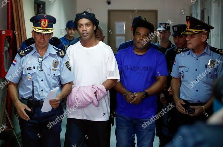 Ronaldinho, Roberto de Assis Moreira. Former soccer star Ronaldinho, second from left, and his brother Roberto de Assis Moreira walks escorted by police officers to declare to judge Clara Ruiz Diaz at Justice Palace in Asuncion, Paraguay,. Ronaldinho and his brother Roberto were alleged to enter to the country with a false Paraguayan passport