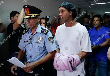 Ronaldinho, Roberto de Assis Moreira. Former soccer star Ronaldinho talks as he walks escorted by Police officers with hands handcuffed to declare to judge Clara Ruiz Diaz at Justice Palace in Asuncion, Paraguay,. Ronaldinho and his brother Roberto de Assis Moreira, right back, were alleged to enter to the country with a false Paraguayan passport