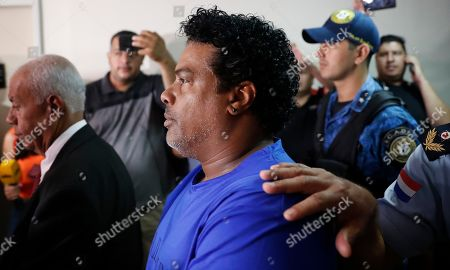 Ronaldinho's brother Roberto de Assis Moreira walks escorted by Police officers to declare to judge Clara Ruiz Diaz at Justice Palace in Asuncion, Paraguay,. Ronaldinho and his brother Roberto were alleged to enter to the country with a false Paraguayan passport