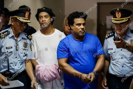 Brazilian former soccer player Ronaldo de Assis Moreira, a.k.a. Ronaldinho (C-L), and his brother Roberto (C-R) are escorted during a new audience at Palace of Justice in Asuncion, Paraguay, 07 March 2020. Ronaldinho and his brother Roberto appeared on 07 March before the judge for the open cause after entering Paraguay with false passports.