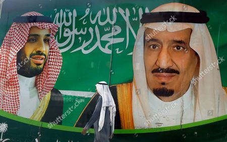 Stock Photo of A man walks past a banner showing Saudi King Salman, right, and his Crown Prince Mohammed bin Salman, outside a mall in Jiddah, Saudi Arabia