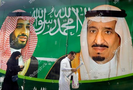 People walk past a banner showing Saudi King Salman, right, and his Crown Prince Mohammed bin Salman, outside a mall in Jiddah, Saudi Arabia