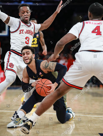Marquette guard Markus Howard (0) is double-teamed by St. John's guards Rasheem Dunn (3) and Greg Williams Jr. (4), during an NCAA college basketball game, at Madison Square Garden in New York