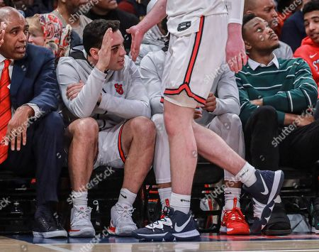 St. John's guard Thomas O'Connell, second from left, sits on the bench with a black-eye as he greets a teammate leaving the floor during an NCAA college basketball game against Marquette, at Madison Square Garden in New York
