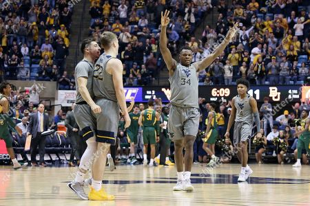 West Virginia guards Jordan McCabe (5), Sean McNeil (22), forward Oscar Tshiebwe (34), and guard Miles McBride (4) celebrate after a score against Baylor during the first half of an NCAA college basketball game, in Morgantown, W.Va