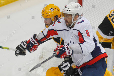 Washington Capitals' Alex Ovechkin (8) tries to get around Pittsburgh Penguins' Jack Johnson (3) during the first period of an NHL hockey game, in Pittsburgh