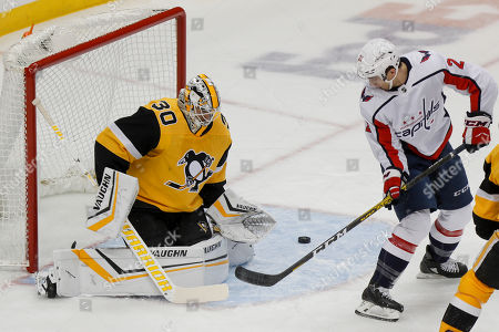 Washington Capitals' Garnet Hathaway (21) tries to direct the puck as Pittsburgh Penguins goaltender Matt Murray (30) defends during the first period of an NHL hockey game, in Pittsburgh