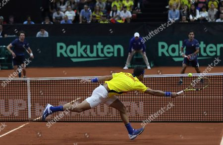 Colombia's Robert Farah returns a ball against Argentina's Horacio Zeballos and Maximo Gonzalez, during their Davis Cup Rakuten Qualifiers tennis doubles match in Bogota, Colombia