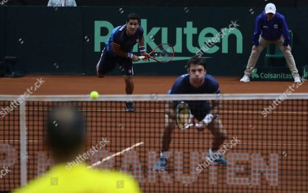 Horacio Zeballos, M'ximo Gonzalez. Argentina's Maximo Gonzalez returns a ball as his partner Horacio Zeballos maintains his position at net, during their Davis Cup Rakuten Qualifiers tennis doubles match against Colombia players Robert Farah and Juan Sebastian Cabal, in Bogota, Colombia, Saturday, March, 7, 2020