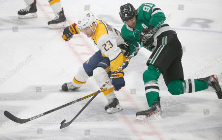 Stock Picture of Nashville Predators right wing Rocco Grimaldi (23) and Dallas Stars center Tyler Seguin (91) battle for the puck during the third period of an NHL hockey game, in Dallas. Nashville won 1-0
