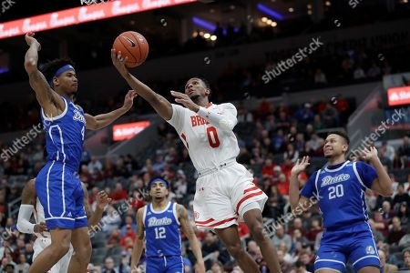 Bradley's Danya Kingsby (0) heads to the basket past Drake's Anthony Murphy, left, Roman Penn (12) and Jonah Jackson (20) during the first half of an NCAA college basketball game in the semifinal round of the Missouri Valley Conference men's tournament, in St. Louis