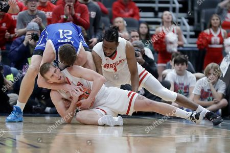 IBradley's Nate Kennell keeps hold of the ball as Drake's Liam Robbins (21) tries to pull it away an Bradley's Ari Boya, right, watches during the first half of an NCAA college basketball game in the semifinal round of the Missouri Valley Conference men's tournament, in St. Louis