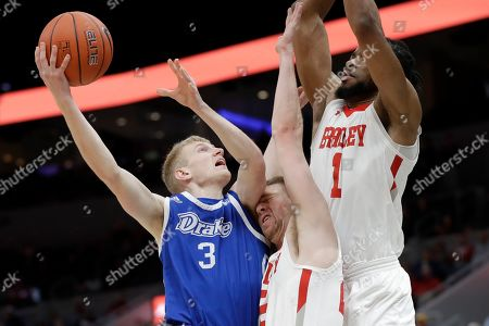 Drake's Garrett Sturtz (3) heads to the basket as Bradley's Nate Kennell and Ari Boya (1) defend during the second half of an NCAA college basketball game in the semifinal round of the Missouri Valley Conference men's tournament, in St. Louis