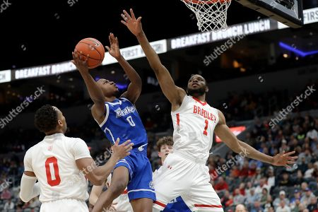 Drake's D.J. Wilkins shoots as Bradley's Danya Kingsby, left, and Ari Boya, right, defend during the second half of an NCAA college basketball game in the semifinal round of the Missouri Valley Conference men's tournament, in St. Louis